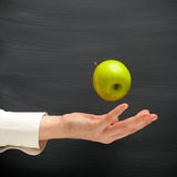 Hand throw an apple. Against blackboard background Royalty Free Stock Images