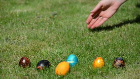 Hand throw colorful eggs on grass. Traditional Easter games stock footage