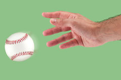 A hand throwing a baseball. With a green background Stock Photography