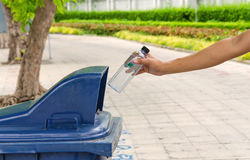 Hand throwing bottle in trash cans Royalty Free Stock Photo