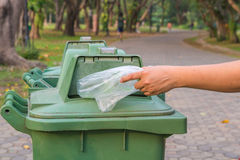 Hand throwing bottle in trash cans Stock Photos