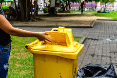 Hand throwing bottle in the yellow litter Bin Royalty Free Stock Image