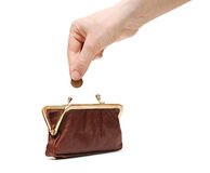 Hand throwing coin in purse Stock Photo