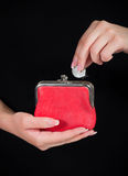 Hand throwing coin in purse on black background Royalty Free Stock Images