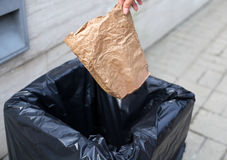 Hand throwing a crumpled paper bag in trash on street Royalty Free Stock Photography