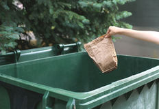 Hand throwing crumpled paper bag in trash on street over tree Stock Photo