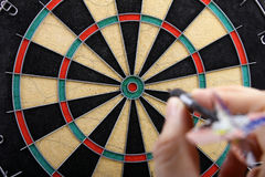 Hand throwing dart. To dartboard Royalty Free Stock Photos