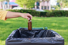 Hand throwing empty glass bottle into the trash Royalty Free Stock Image