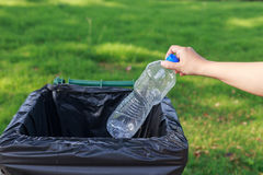 Hand throwing empty plastic bottle into the trash Royalty Free Stock Photography