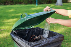 Hand throwing empty plastic bottle into the trash Stock Photos