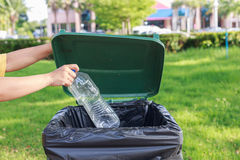Hand throwing empty plastic bottle into the trash Stock Photography