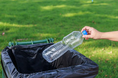 Hand throwing empty plastic bottle into the trash Royalty Free Stock Images