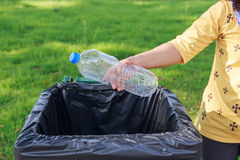 Hand throwing empty plastic bottle into the trash Stock Images