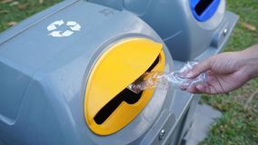 Hand throwing empty plastic bottle into the trash. Close up hand throwing empty plastic bottle into the trash with sunshine and the park background Royalty Free Stock Photos