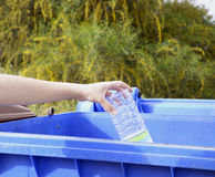 Hand throwing empty plastic bottle in trash Stock Image