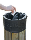 Hand throwing paper in the litterbin. Royalty Free Stock Photos
