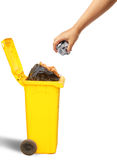 Hand throwing paper into the yellow recycle trash. Ecology concept Stock Images