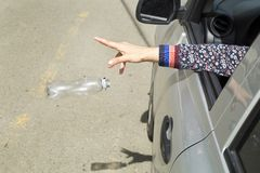 Throw plastic bottle from the car. Hand throwing plastic bottle on the road royalty free stock image