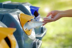 Hand throwing plastic water bottle in recycle bin royalty free stock image