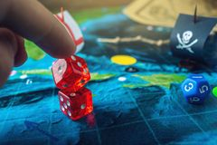 Hand throwing red dice on the world map of the playing field handmade Board games with a pirate ship. The game of battleship stock photo