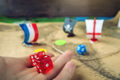 Hand throwing red dice on the world map of the playing field handmade Board games with a pirate ship. The game of battleship stock images