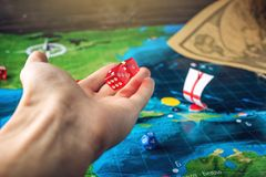 Hand throwing red dice on the world map of the playing field handmade Board games with a pirate ship. The game of battleship stock photography
