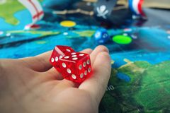 Hand throwing red dice on the world map of the playing field handmade Board games with a pirate ship. The game of battleship royalty free stock photos