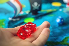 Hand throwing red dice on the world map of the playing field handmade Board games with a pirate ship. The game of battleship stock image