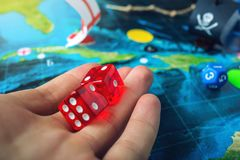 Hand throwing red dice on the world map of the playing field handmade Board games with a pirate ship. The game of battleship royalty free stock images
