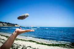 Hand throwing a stone. In the air with beach as background Stock Photos