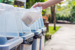 Hand throws away waste material into trash container Royalty Free Stock Photos