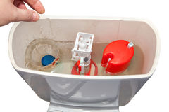Hand throws blue cleaner tablet in flush tank toilet bowl. Royalty Free Stock Photography