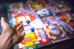 Hand throws the dice on the background of Board games Royalty Free Stock Photos