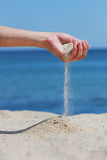 Hand throws sand Royalty Free Stock Image