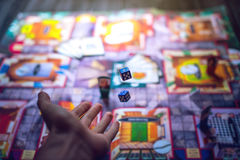 Free Hand Throws The Dice On The Background Of Board Games Stock Photography - 84994152