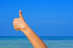 Hand with thumb up on blue sky and sea background Royalty Free Stock Images