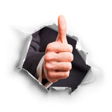Hand with thumb up breaking through wall Stock Images