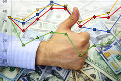 Hand with thumb up on dollars with financial graph Royalty Free Stock Image