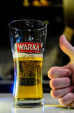 Hand with thumb up in front of the beer in glass. Picture shows hand with thumb up in front of lager beer in glass and blurred backgroud Royalty Free Stock Image