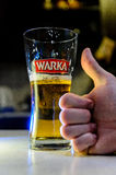 Hand with thumb up in front of the beer in glass. Picture shows hand with thumb up in front of lager beer in glass and blurred backgroud Stock Photography