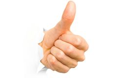 Hand with thumb up has broken through a paper. Stock Photo