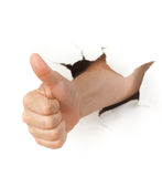 Hand with thumb up through a hole in paper Stock Image
