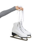 Hand with thumb up sign holding woman ice skates. Woman hand hold ice skates isolated on a white background Stock Photo