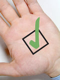 Hand with tick sign. Male hand with green tick symbol Stock Photo