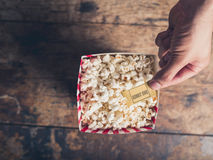 Hand with ticket and popcorn Stock Image