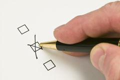 Hand ticking a check box with a pen Stock Image