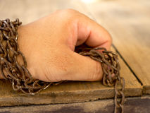 The hand are tied with rusty chain for not to escape.  Royalty Free Stock Image