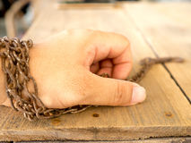 The hand are tied with rusty chain for not to escape. The hand are tied with rusty chain for not to escape Stock Photos