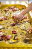 Hand till att försöka att ställa in en myntbaht på bild av buddha& x27; s-fotspår Arkivbild