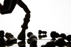Hand tilting the figure of the king on the chessboard. Focus on the figure of King.Soft focus Royalty Free Stock Photos